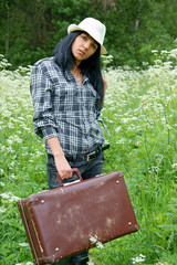 Pretty girl with suitcase outdoor in summer