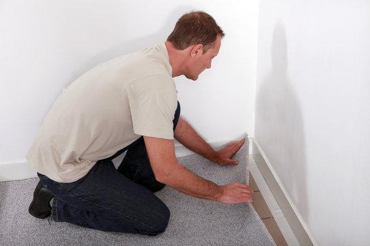 Man installing carpet in room