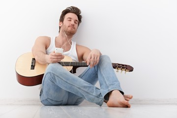 Young guitarist listening music eyes closed