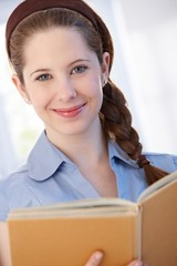 Smiling woman with book at home