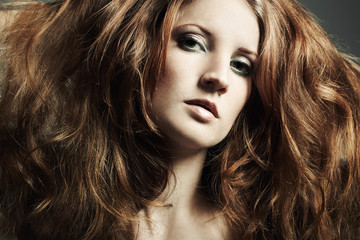 Fashion portrait of a young beautiful redheaded woman. Close-up
