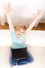 junge Frau mit Computer, die Arme zur Kamera ausgestreckt