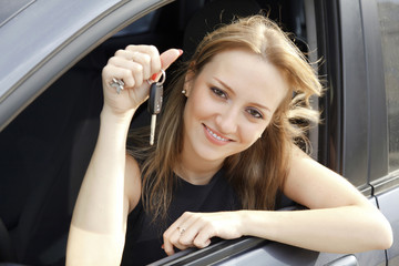 The happy woman showing the key of her new car