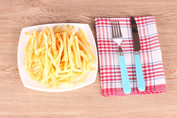 French fries and cutlery on a wooden background