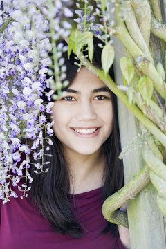 Beautiful young teen girl standing under wisteria vines