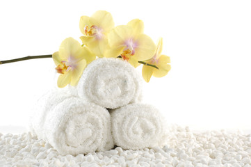 Orchids on White spa towels on white pebble
