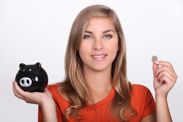 Teenage girl holding piggy bank