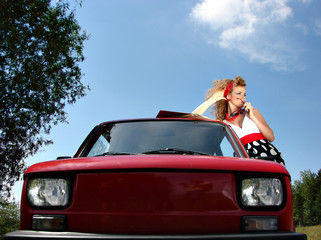 Girl in dress with red comapct car