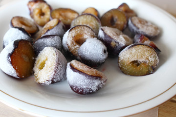 Frozen, defrosting plums on a plate
