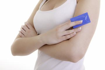 Verschränkte junge Dame mit blauem Kondom