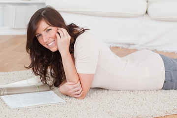 Young beautiful woman reading a magazine while lying on a carpet