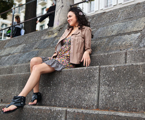 Portrait of young beautiful Latina sitting on a stairs