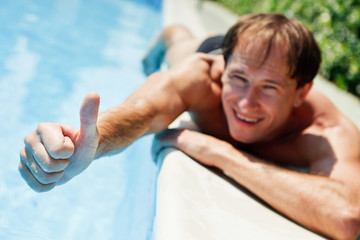 man showing  a thumbs up near swimmingpool