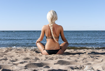 blonde girl in bathing suit sits on the beach and meditate