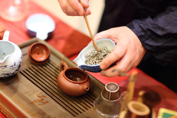 Man pours tealeafs by bamboo Tea Scoop