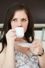 girl drinks coffee in cafe in shopping center
