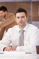 Portrait of casual office worker sitting at desk