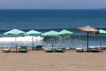 Sun chairs and umbrellas against Mediterranean Sea - Crete