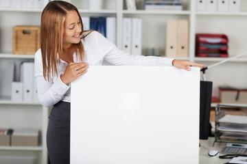 junge frau im büro schaut auf weißes schild