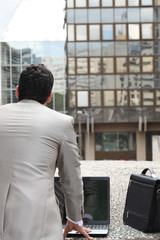 Back view of a businessman standing outside with computer