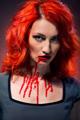 Portrait of a redhead woman with blood in her lips and neck