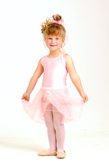 Little smiley girl wearing a pink ballet outfit is dancing