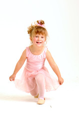 Little smiley girl wearing a pink ballet outfit