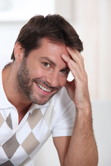 Close-up of man sitting at home smiling with hand to head