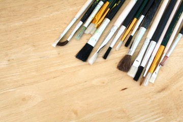 Artist piant brushes on vertical pine wood background
