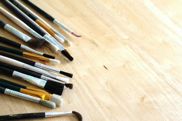 Mixed artists paint brushes on pine table with space