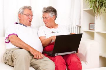 Seniorin erklärt ihrem Ehepartner den Computer