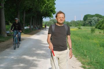 Blinder Mann mit Langstock unterwegs im Freien