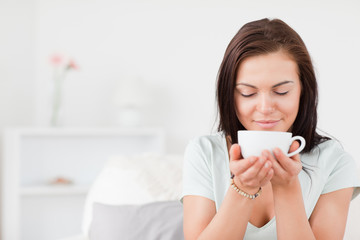 Delighted dark-haired woman drinking tea