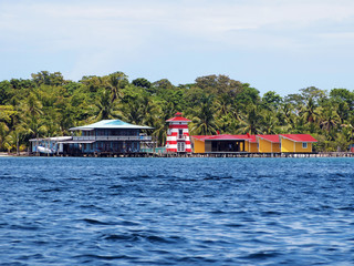 Bungalows, house and a lighthouse on the sea shore of a tropical Caribbean island, Bocas del toro, Panama, Central America
