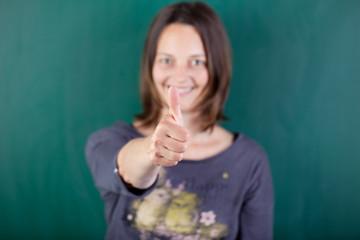 lächelnde lehrerin vor der tafel zeigt daumen hoch