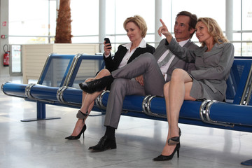 Businessmen and women in departure lounge.