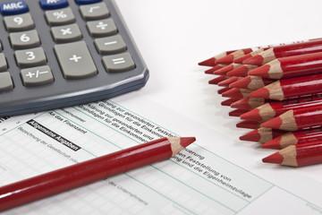 Steuererklärung mit Rotstift und Taschenrechner