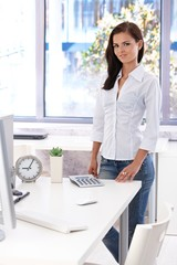 Female office worker standing by desk smiling