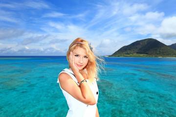 伊平屋の海辺で寛いでいる笑顔の女性