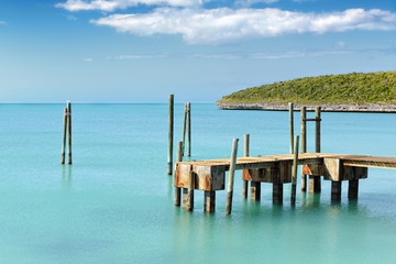 Mooring posts and pontoon leading in turquoise blue sea