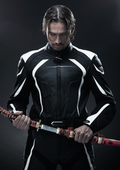 Handsome man holding a samurai sword