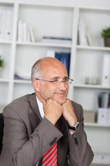 lächelnder mann sitzt im büro am schreibtisch