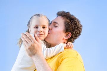man kisses his daughter