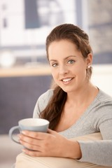 Attractive woman drinking tea on sofa smiling