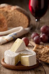 Traditional Normandy Camembert cheese with homemade bread, glass