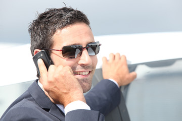 Elegant businessman on phone outdoors