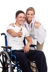 pflegerin und rollstuhlfahrer zeigen daumen hoch