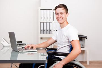junger mann im rollstuhl am arbeitsplatz