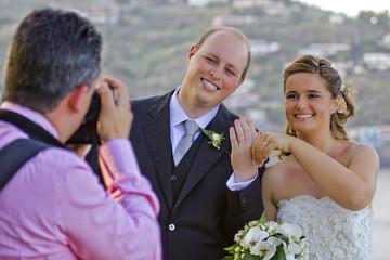 Fotografo con gli sposi che mostrano le fedi