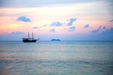Boat in a landscape of sunset colors over the ocean.